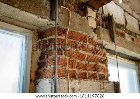 The use of aluminum rails for preparing walls for applying plaster. Installation of guides for plaster. Installation of metal lighthouses on a brick wall. #1611197626