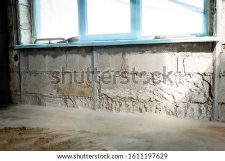 The use of aluminum rails for preparing walls for applying plaster. Installation of guides for plaster. Installation of metal lighthouses on a brick wall. #1611197629