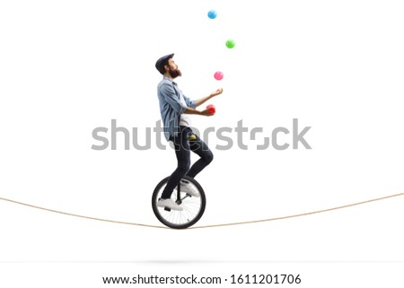 Full length profile shot of a bearded male hipster juggler with balls riding a unicycle on a rope isolated on white background #1611201706