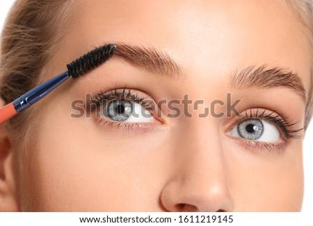 Young woman undergoing eyebrow correction procedure, closeup Royalty-Free Stock Photo #1611219145