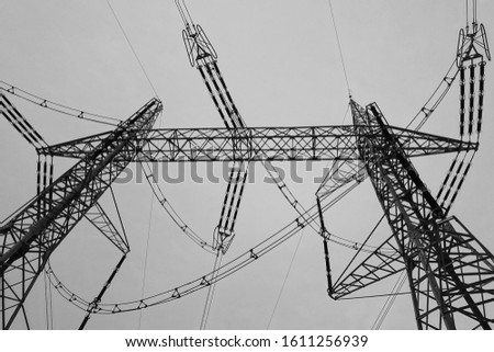 High voltage masts and silhouette of mast with streaky juniper. #1611256939
