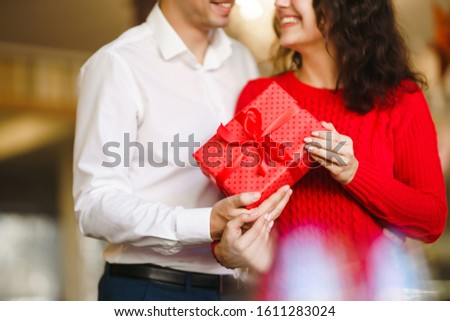 Man gives to his woman a gift box with red ribbon. A loving couple cuddles and celebrating Valentine's Day in the restaurant. Valentine's Day, holiday and surprise concept. Relationship and love. #1611283024