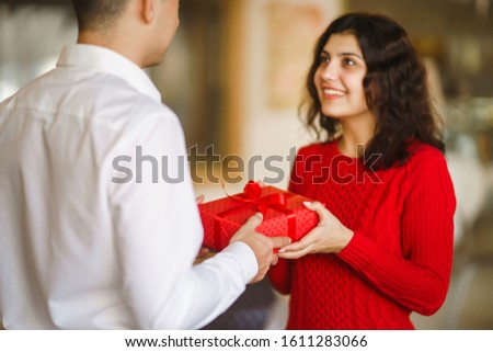 Man gives to his woman a gift box with red ribbon. A loving couple cuddles and celebrating Valentine's Day in the restaurant. Valentine's Day, holiday and surprise concept. Relationship and love. #1611283066