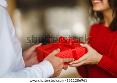 Man gives to his woman a gift box with red ribbon. A loving couple cuddles and celebrating Valentine's Day in the restaurant. Valentine's Day, holiday and surprise concept. Relationship and love. #1611286963