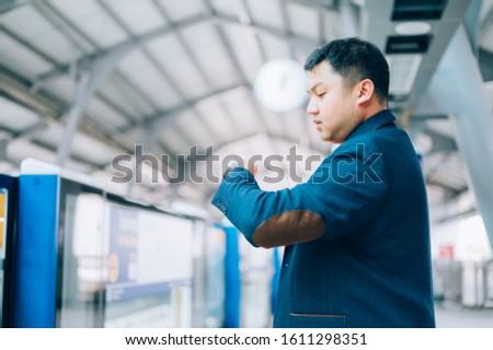 Asian businessman looking at his watch, waiting train platform #1611298351