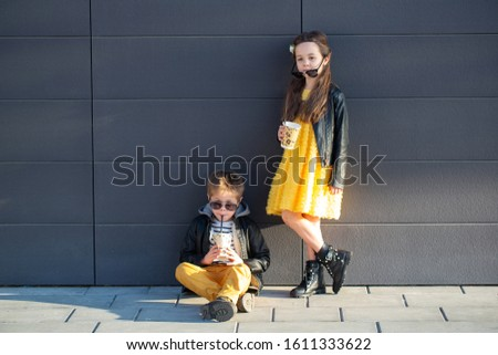 Little kids walk together and drink hot drinks. Stylishly dressed fashionable kids. A teenager in yellow jeans, and a girl in a yellow dress. #1611333622