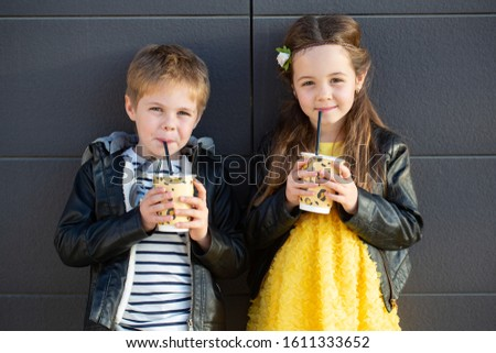 Little kids walk together and drink hot drinks. Stylishly dressed fashionable kids. A teenager in yellow jeans, and a girl in a yellow dress. #1611333652