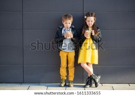 Little kids walk together and drink hot drinks. Stylishly dressed fashionable kids. A teenager in yellow jeans, and a girl in a yellow dress. #1611333655