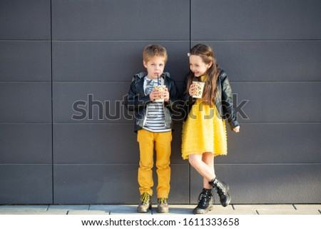 Little kids walk together and drink hot drinks. Stylishly dressed fashionable kids. A teenager in yellow jeans, and a girl in a yellow dress. #1611333658