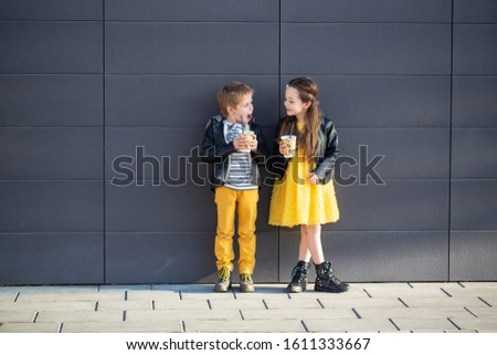 Little kids walk together and drink hot drinks. Stylishly dressed fashionable kids. A teenager in yellow jeans, and a girl in a yellow dress. #1611333667
