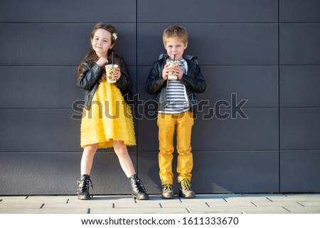 Little kids walk together and drink hot drinks. Stylishly dressed fashionable kids. A teenager in yellow jeans, and a girl in a yellow dress. #1611333670