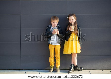 Little kids walk together and drink hot drinks. Stylishly dressed fashionable kids. A teenager in yellow jeans, and a girl in a yellow dress. #1611333673