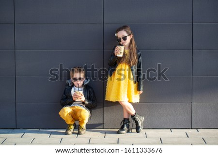 Little kids walk together and drink hot drinks. Stylishly dressed fashionable kids. A teenager in yellow jeans, and a girl in a yellow dress. #1611333676