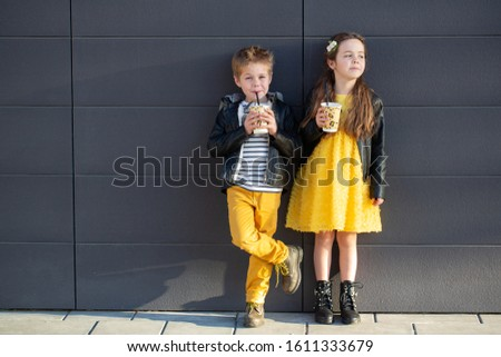 Little kids walk together and drink hot drinks. Stylishly dressed fashionable kids. A teenager in yellow jeans, and a girl in a yellow dress. #1611333679