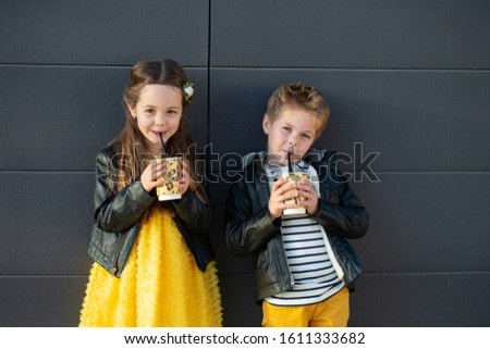 Little kids walk together and drink hot drinks. Stylishly dressed fashionable kids. A teenager in yellow jeans, and a girl in a yellow dress. #1611333682