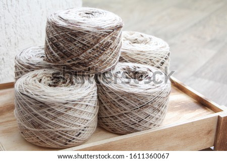 Melange yarn skeins on a wooden box in a light room. Beige-brown colored yarn. Bobbins of yarn. #1611360067