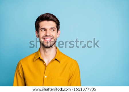 Photo of cheerful nice creative young guy freelancer in yellow shirt looking into empty space smiling toothily isolated over blue pastel color background #1611377905