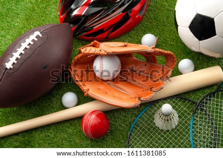 Sports shop, youth athletics and team sport competition conceptual idea with various types balls (soccer, baseball, football, golf ball), wooden bat and bike helmet isolated on green grass background #1611381085