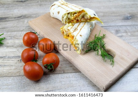 Pieces of cutted thin Armenian pita bread or lavash wrapped tomatoes, cottage cheese or curd, chicken meat, tomatoes and herbs - dill, onion, parsley with vintage knife on cutting board. #1611416473