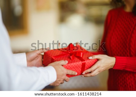 Valentine's Day, holiday and surprise concept. Man gives to his woman a red gift box. Sweet couple celebrate their anniversary. Relationship and love concept. #1611438214