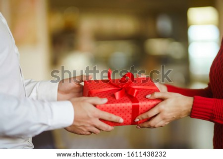 Valentine's Day, holiday and surprise concept. Man gives to his woman a red gift box. Sweet couple celebrate their anniversary. Relationship and love concept. #1611438232