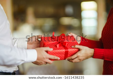 Valentine's Day, holiday and surprise concept. Man gives to his woman a red gift box. Sweet couple celebrate their anniversary. Relationship and love concept. #1611438235