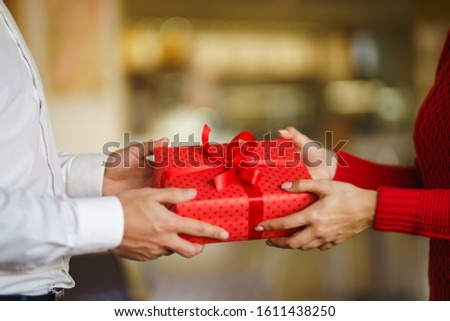 Valentine's Day, holiday and surprise concept. Man gives to his woman a red gift box. Sweet couple celebrate their anniversary. Relationship and love concept. #1611438250