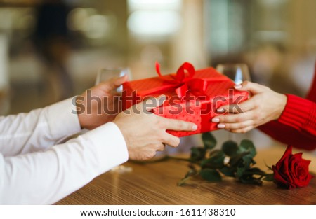 Valentine's Day, holiday and surprise concept. Man gives to his woman a red gift box. Sweet couple celebrate their anniversary. Relationship and love concept. #1611438310