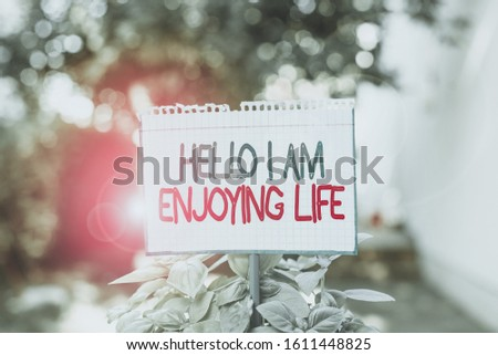 Word writing text Hello I Am Enjoying Life. Business concept for Happy relaxed lifestyle Enjoy simple things Plain empty paper attached to a stick and placed in the green leafy plants. #1611448825