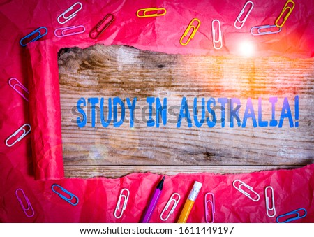 Handwriting text writing Study In Australia. Concept meaning going into foreign country order complete your studies Stationary and torn cardboard placed above a wooden classic table backdrop. #1611449197