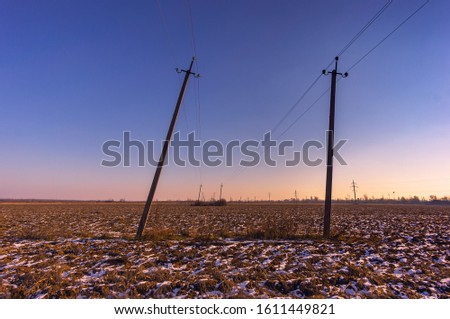 The falling electric pole on the plowed field. Winter evening, snow among earth lumps. The clear sky turns pink at the horizon #1611449821