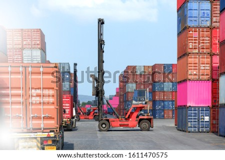 Container handlers are loading containers into trucks. #1611470575