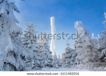 Frozen television or cellular tower in heavy snow near ski center. Telecommunication towers with dish and mobile antenna against blue sky in winter mountains. #1611482056