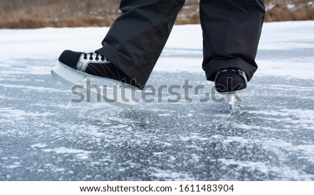 Legs of a man in men's skates on the ice of a wild river. Winter outdoor recreation in the countryside. #1611483904