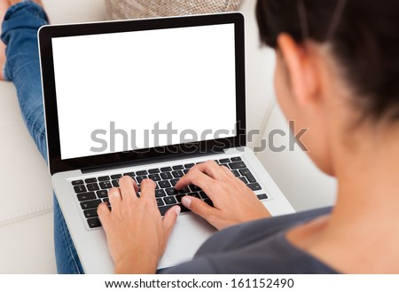 Close-up Of Young Woman Using Laptop On Couch Royalty-Free Stock Photo #161152490
