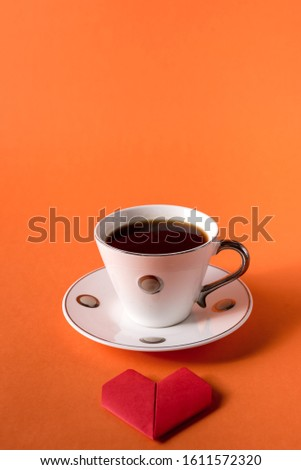 cup of coffee and heart made of paper on orange trendy background with space for text #1611572320