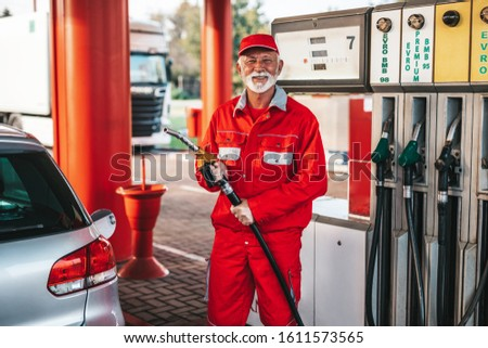 Handsome senior with beard man working on gas station #1611573565