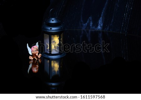 The little toy angel, small lamp,  black background. Mysticism. Mystical atmosphere. Esoteric concept #1611597568