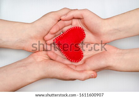 Red heart in the hands of a loving couple of man and woman on a white background. Valentine's Day, creating a family, love, relationships. #1611600907