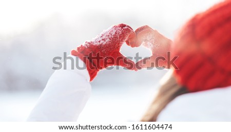 Woman making heart symbol with snowy hands in red gloves, sunny winterday, sun lights, Valentines day, Love concept.