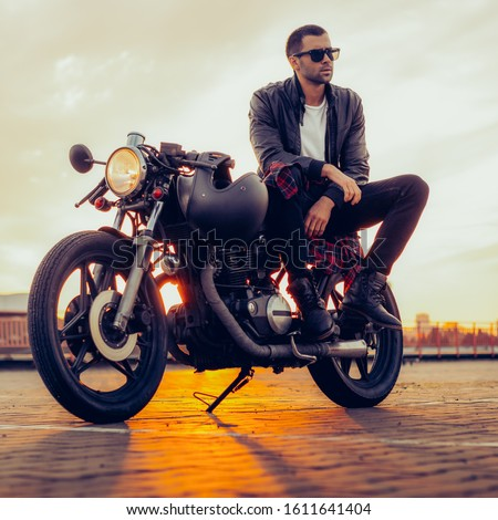Handsome rider man with beard and mustache in black leather biker jacket and sunglasses sit on classic style cafe racer motorcycle. Bike custom made in vintage garage. Brutal fun urban lifestyle. Royalty-Free Stock Photo #1611641404