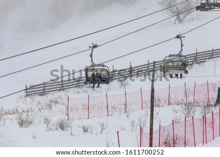 People climbing a cable car downhill in a snowfall #1611700252