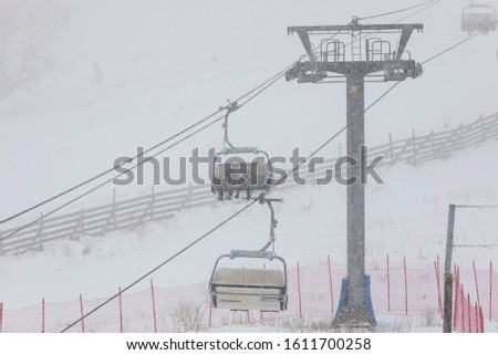 People climbing a cable car downhill in a snowfall #1611700258