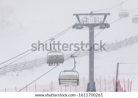 People climbing a cable car downhill in a snowfall #1611700261