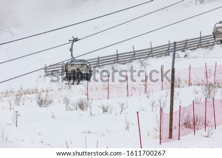 People climbing a cable car downhill in a snowfall #1611700267