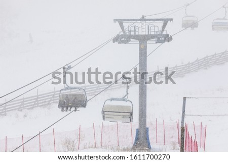People climbing a cable car downhill in a snowfall #1611700270