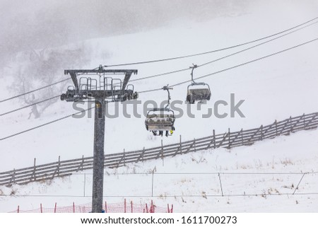 People climbing a cable car downhill in a snowfall #1611700273