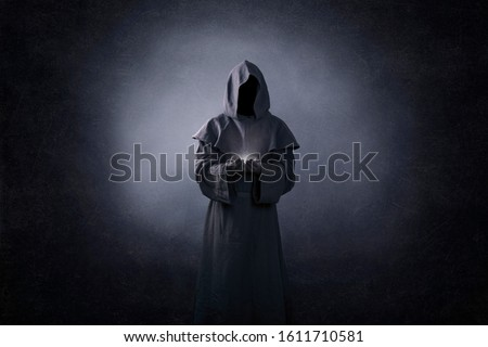 Ghostly figure with light in hands in the dark Royalty-Free Stock Photo #1611710581