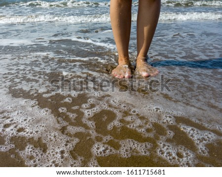 Woman legs in sea water. Closeup of woman legs on sea shore. Summer, beach, leisure and body part concept - closeup of woman legs on sea shore #1611715681