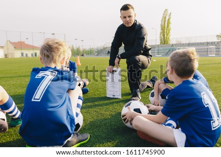 Young Coach Explaining Soccer Positions and Match Tactics to Youth. Kids Football Team Coaching. Children on Soccer Training Royalty-Free Stock Photo #1611745900